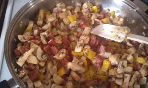 Adding in the pepperoni, mushrooms and bell peppers.