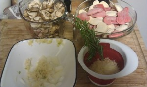 My ingredients starting from top left: 2 cups chopped cremini mushrooms, red and white heart shaped cheese ravioli, parmesean cheese, two sprigs of rosemary, and chopped onions and garlic.