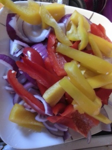 One purple onion, one yellow pepper and one red pepper. Chopped and ready to go.